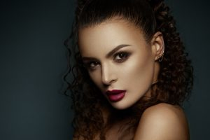 Beautiful face of a fashion model with black eyes.Curly hair. Red lips.